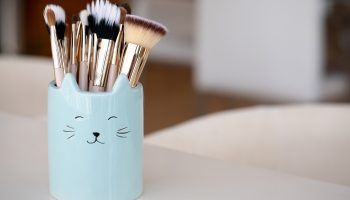 A baby blue makeup cat holder with cat ears and printed face on the holder with makeup brushes in it.